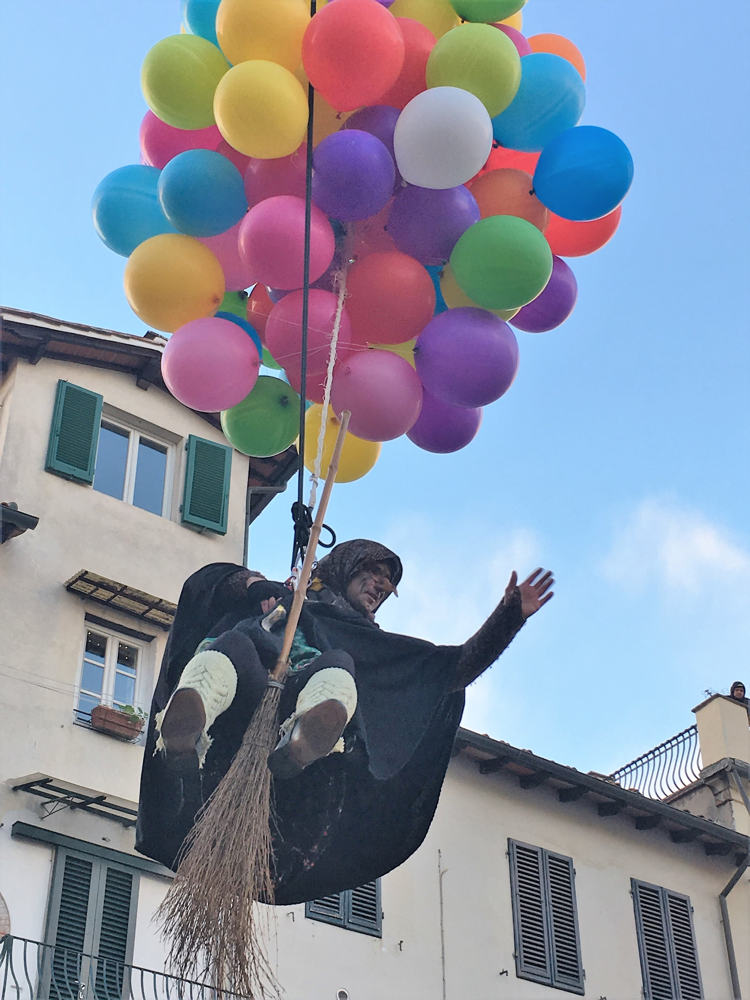 Befana waves to the crowd as she descends on Lucca, January 2017.