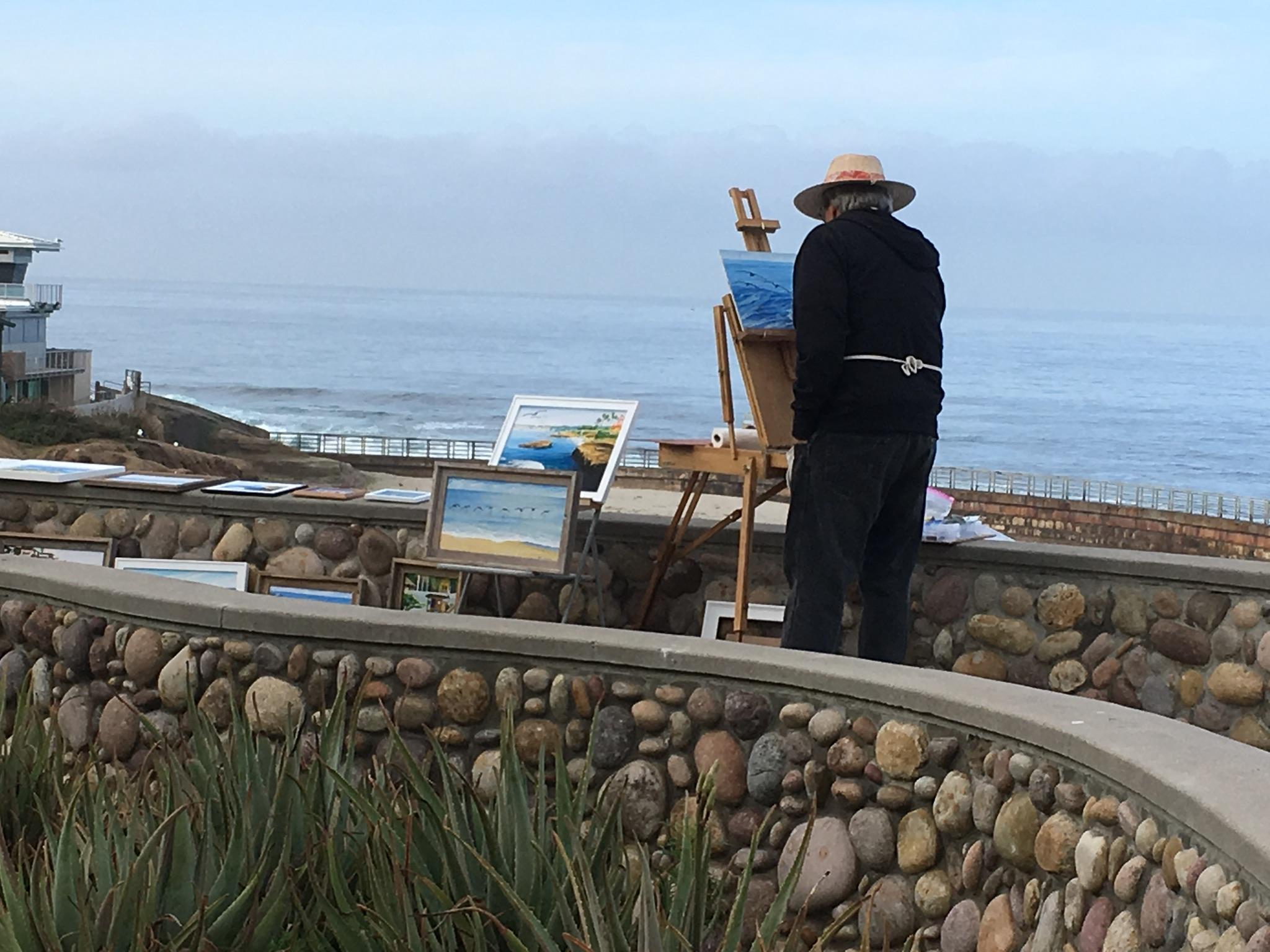 An artist paints en plain air along the coast in La Jolla.