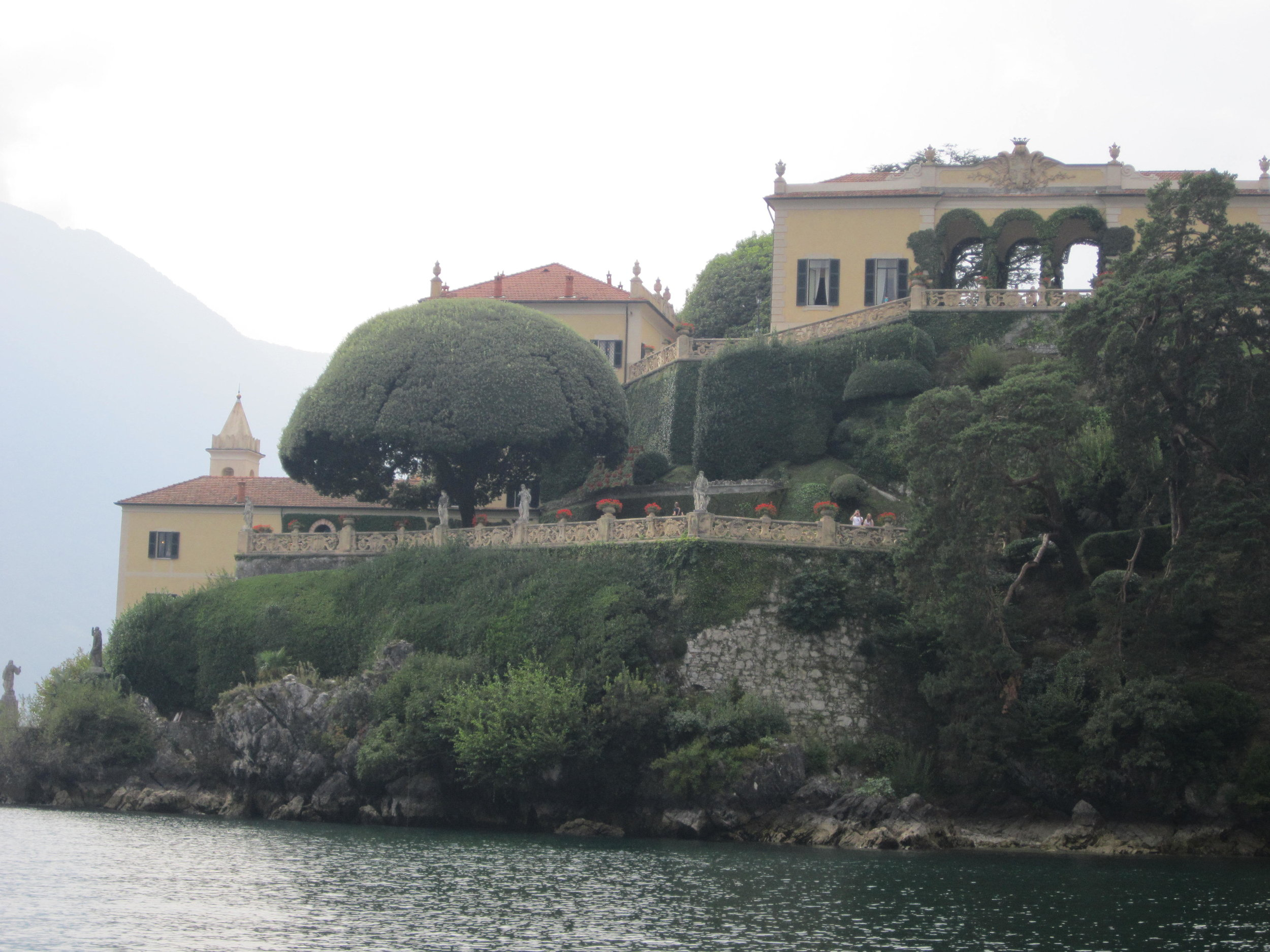 Villa del Balbianello as seen from the lake. The three arches of the loggia, which are flanked by the map room and the library, lie at the top right of the photo. Both loggia rooms, as well as the interior of the villa, can be seen on a guided tour of the property.
