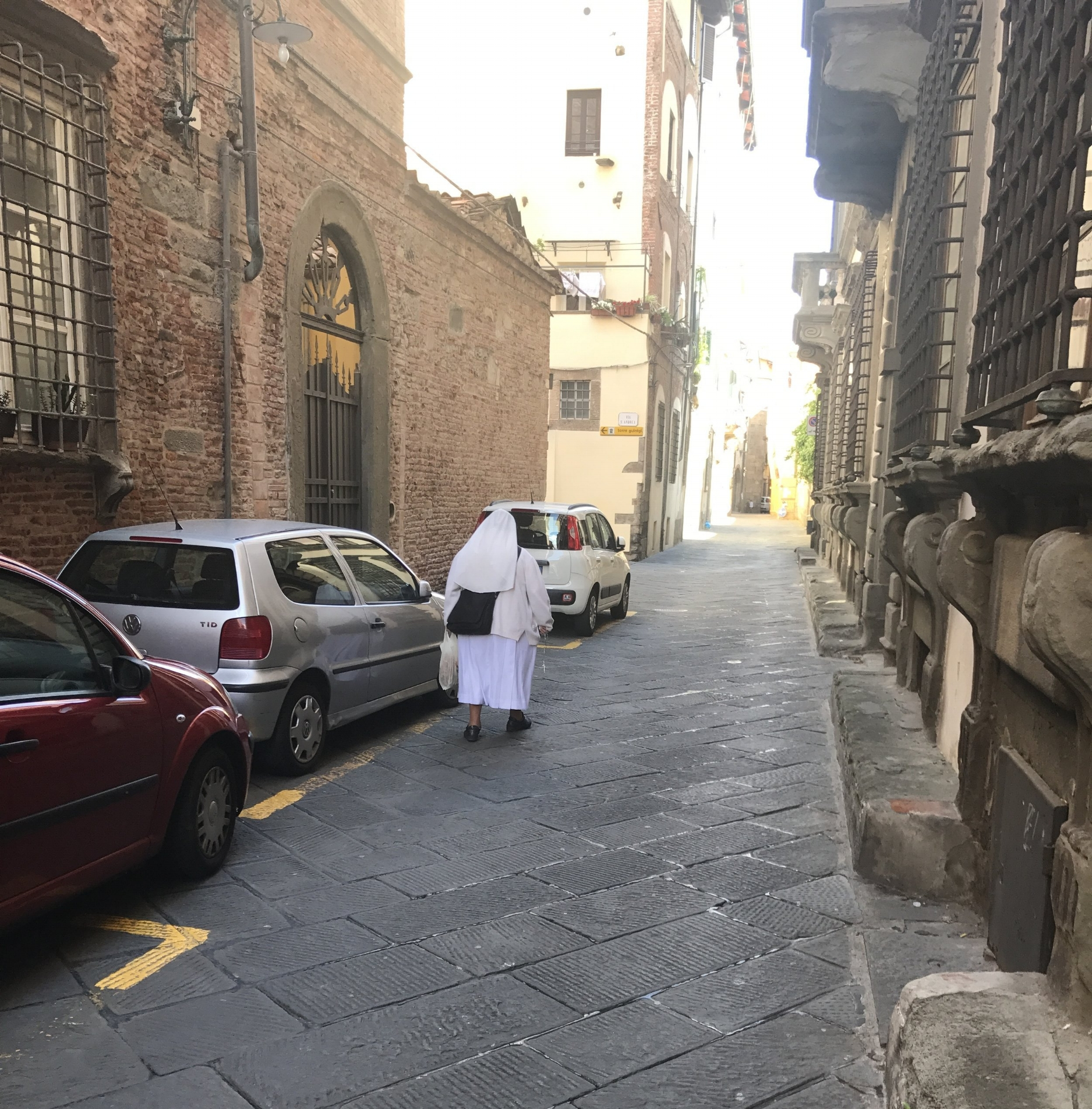 A nun walks toward a sun-splashed area of town.