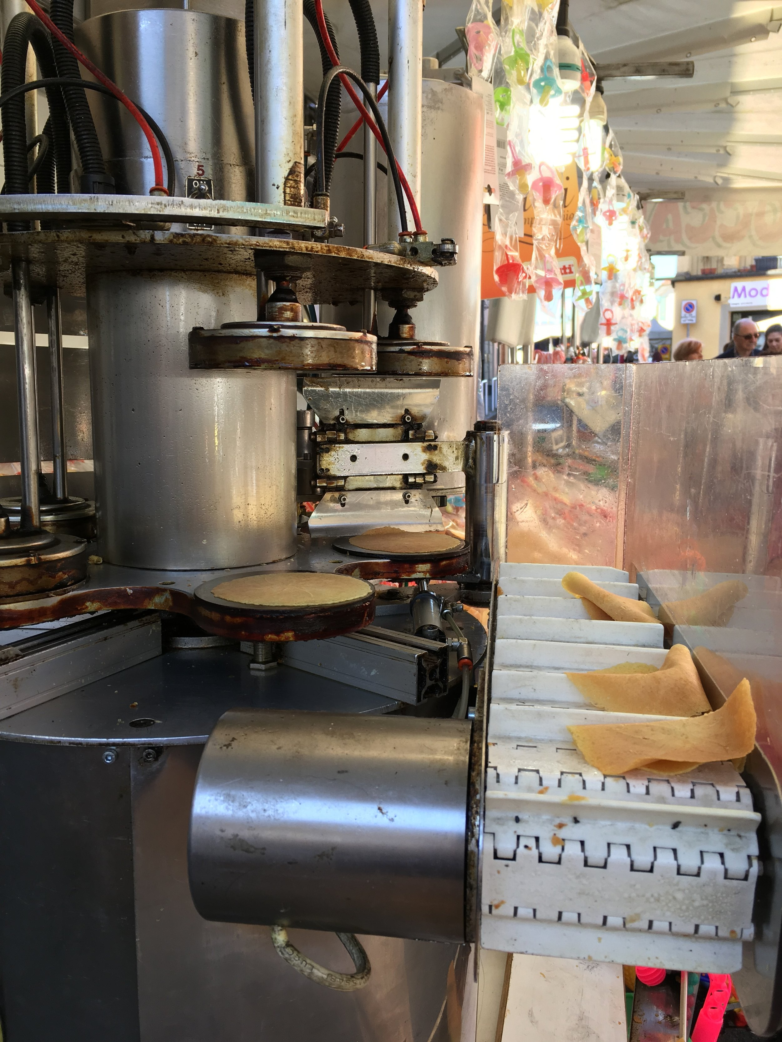 The wafers are cooked individually on the small griddles of the machine. This one rotates and drops them onto the conveyor belt for packaging.I think they are best hot off the griddle!