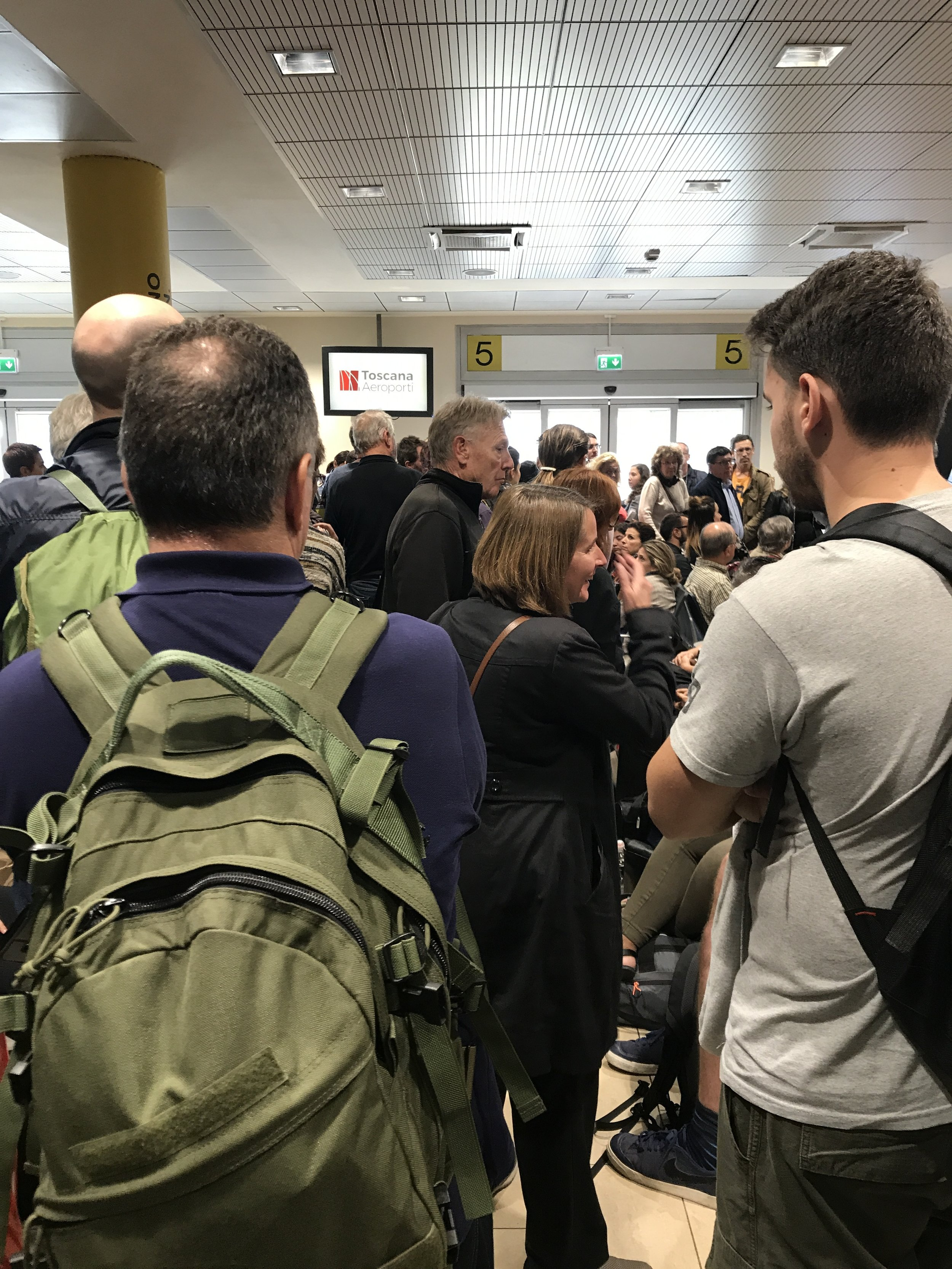 Travelers wait to learn whether their flight has been delayed or canceled at the Florence airport.