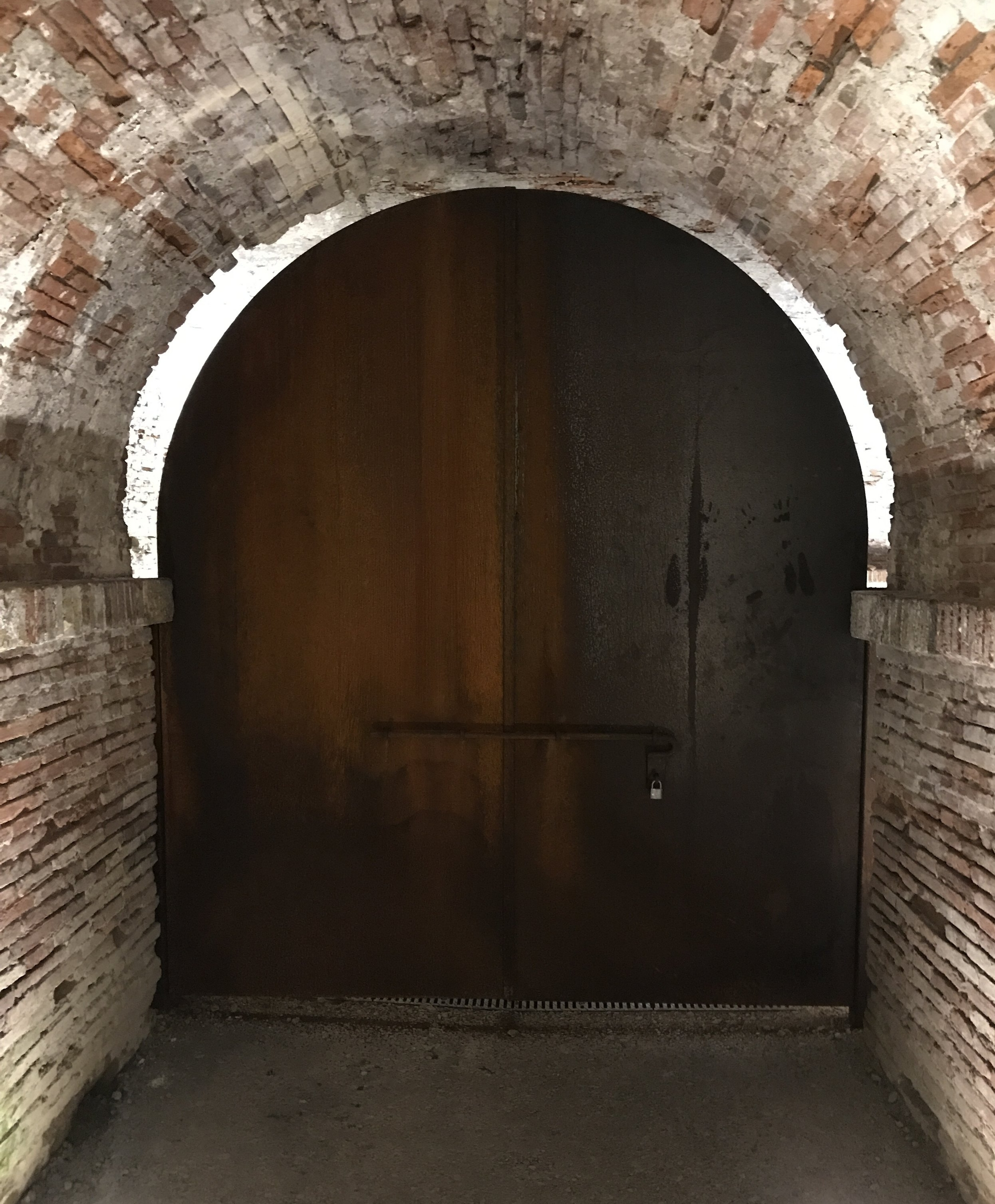 At the end of a passageway is a beautiful wooden door.