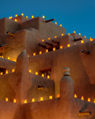 Luminarias, which are called farolitos in northern New Mexico, adorn an adobe building in New Mexico. These simple paper bags are filled with sand and also contain a votive candle, providing a magical glow on Christmas Eve.