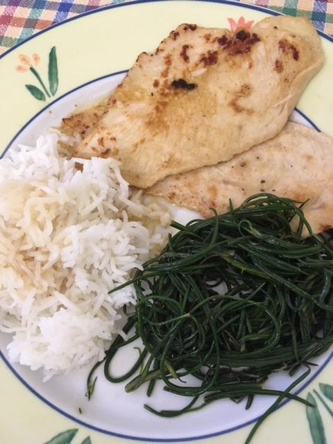 Sautéed agretti alongside pan-sautéed lemon chicken and rice.