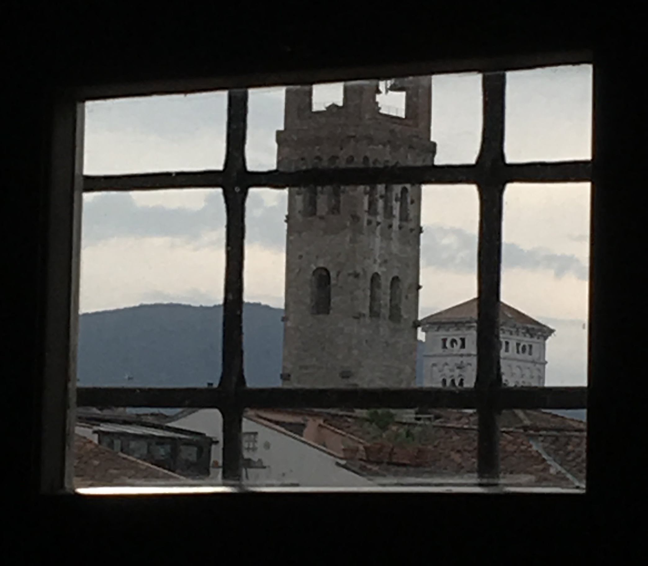 The clock tower and the bell tower of the church of San Michele as seen through a small bedroom window