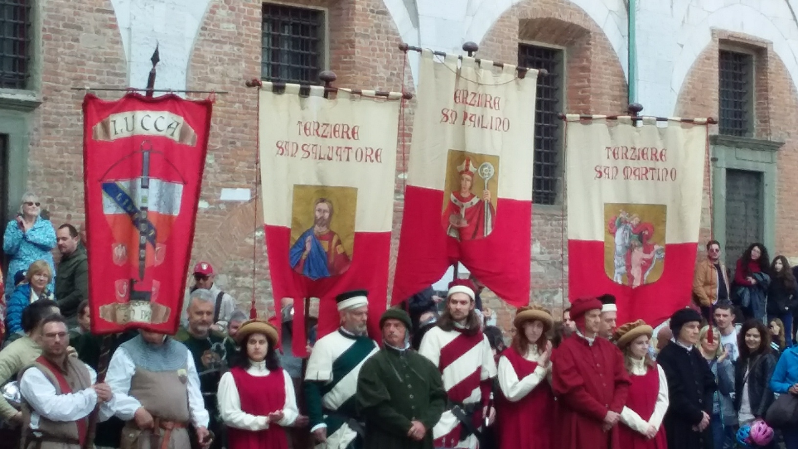 These banners represent Lucca and the three terziere into which it was divided in the 1400s- each named for the major church in the neighborhood (San Salvatore, San Paolino, and San Martino).