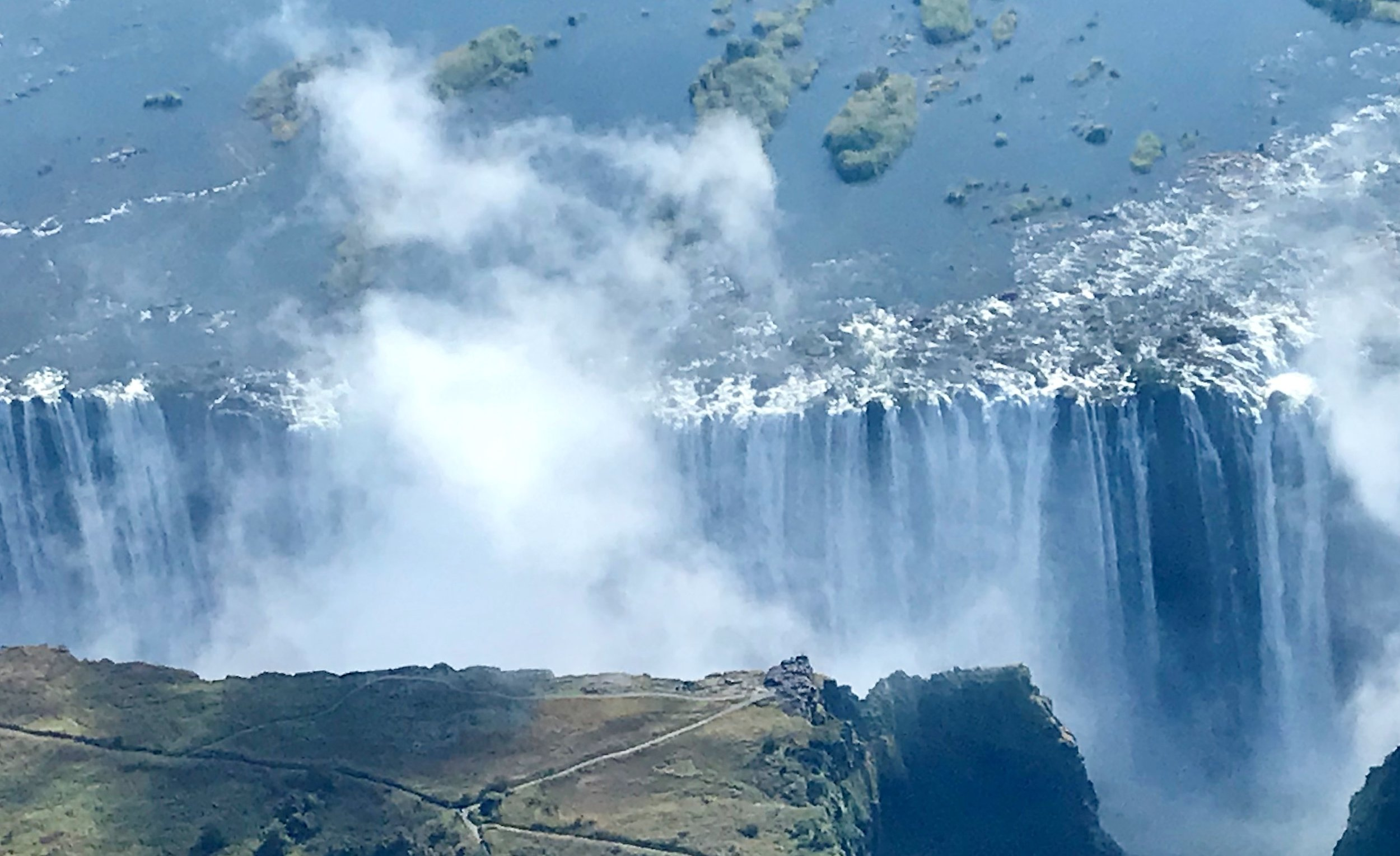 The spray from Victoria Falls rises like a huge puff of smoke.