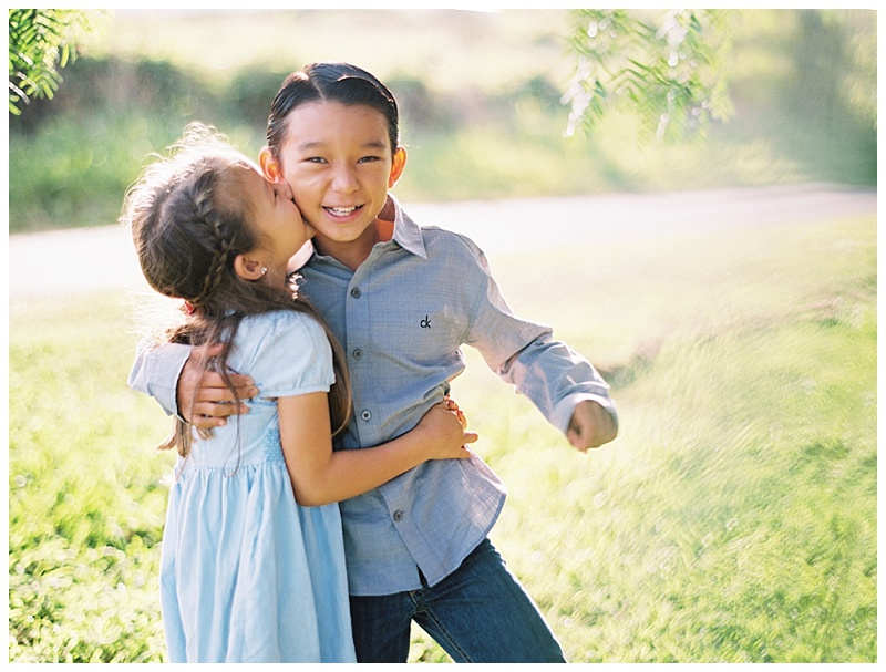 family-photographer-brother-sister-hugging-kiss-on-cheek-smiling.jpg