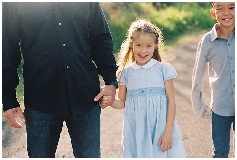 Family-photographer-girl-blue-dress-smiling-holidng-dads-hand.jpg