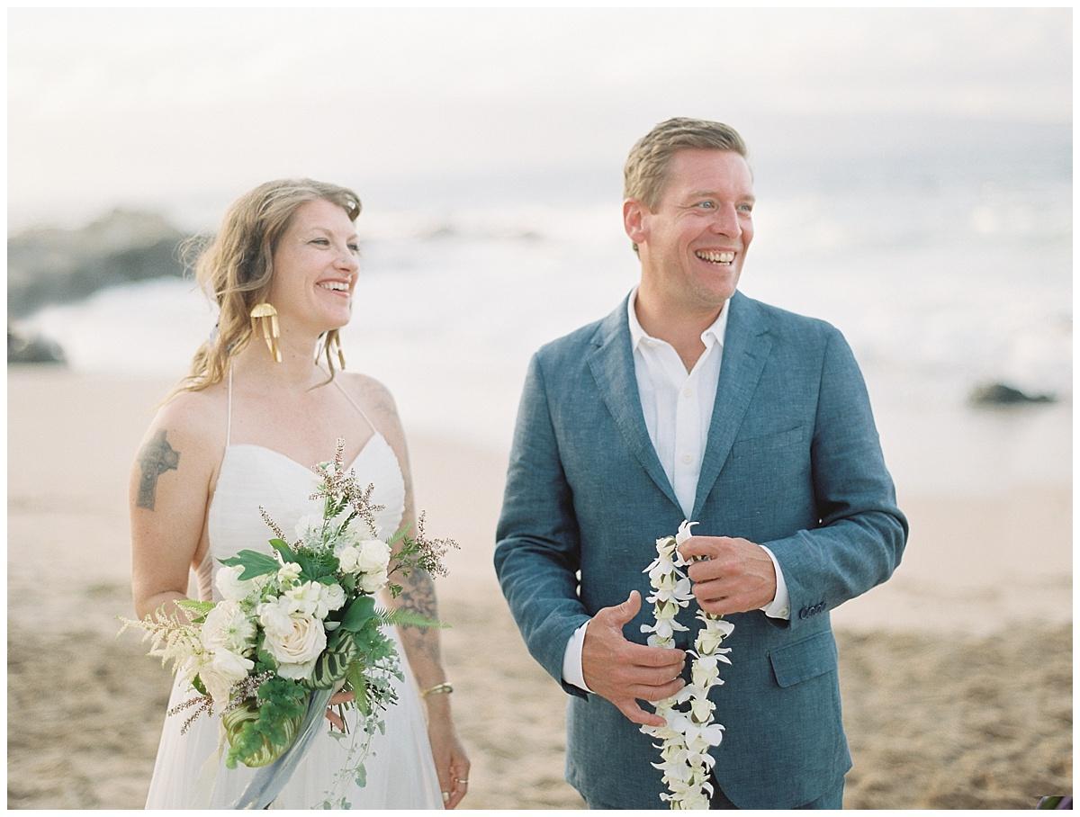 beach-elopement-bride-groom-blue-suit-laughing.jpg