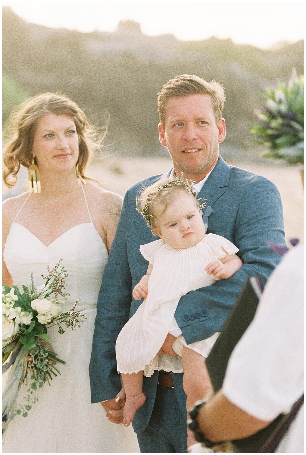 beach-elopement-bride-groom-baby-girl-looking-at-officiant.jpg