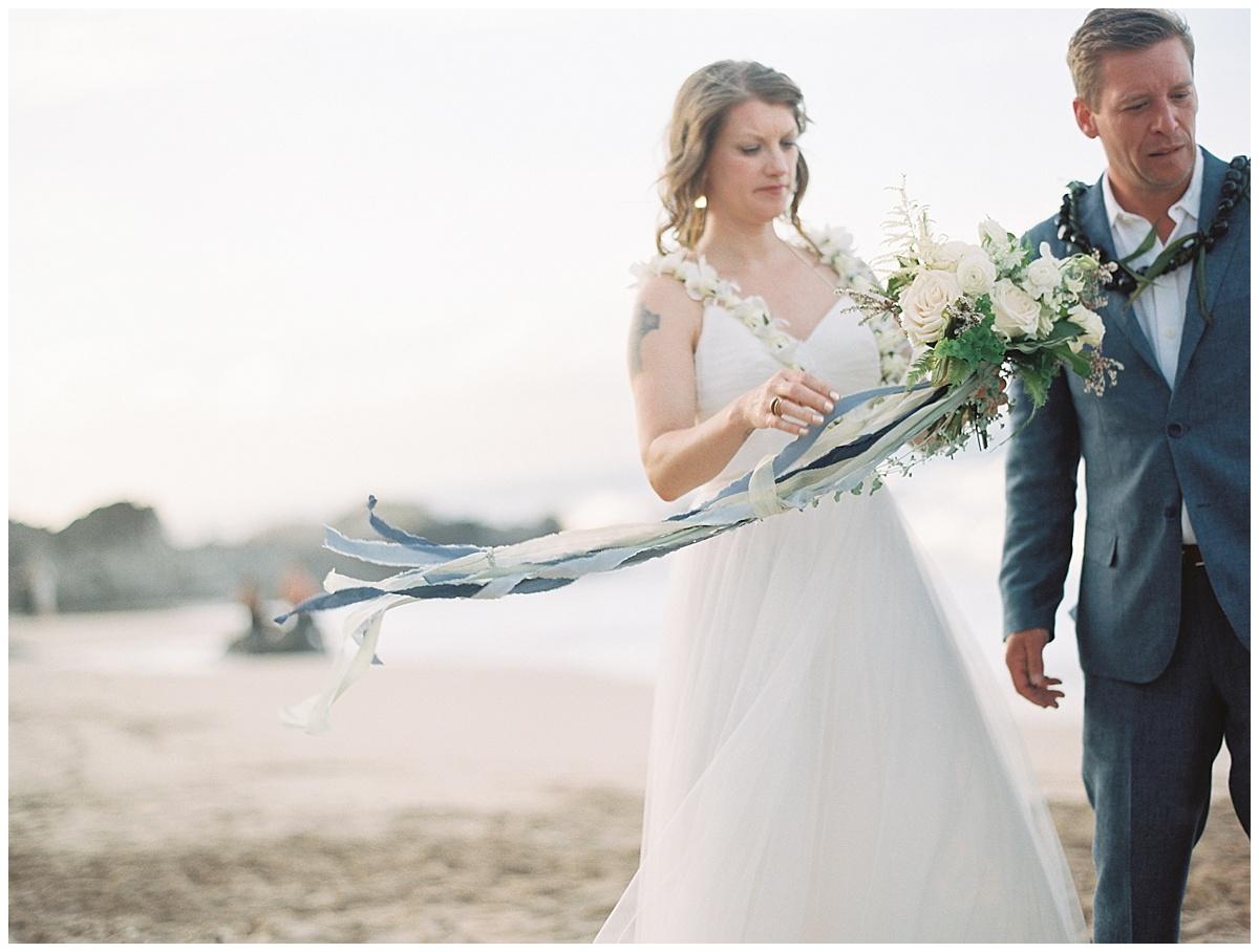 beach-elopement-bride-groom-bouquet-blue-ribbon-blowing-in-wind.jpg