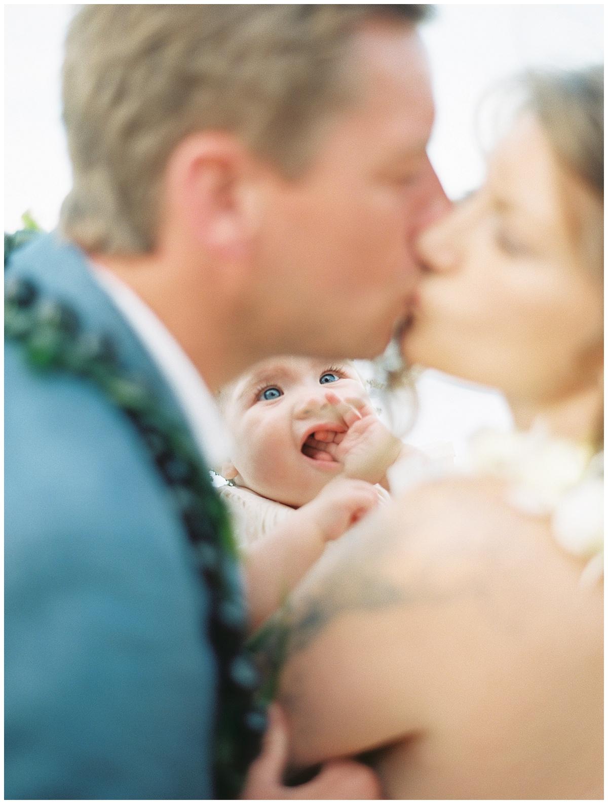 beach-elopement-bride-groom-kiss-while-daughter-watches.jpg