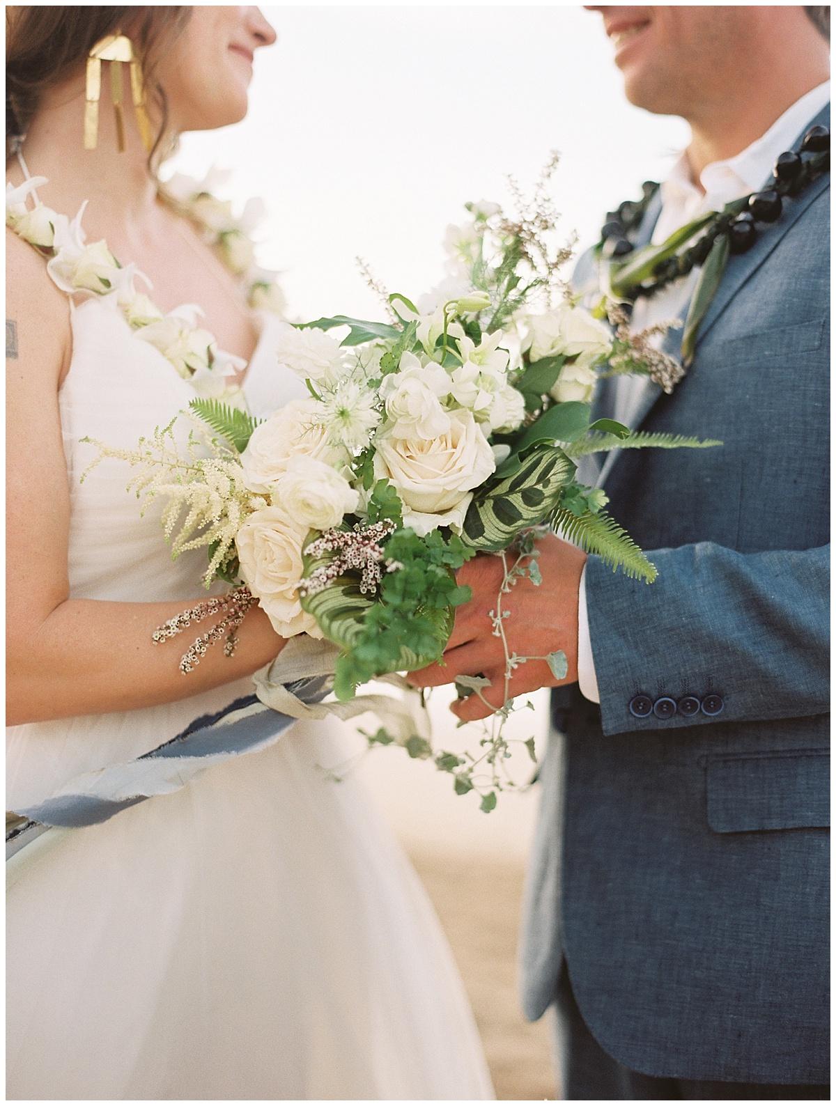 beach-elopement-bride-groom-holding-hands-white-flower-bouquet.jpg