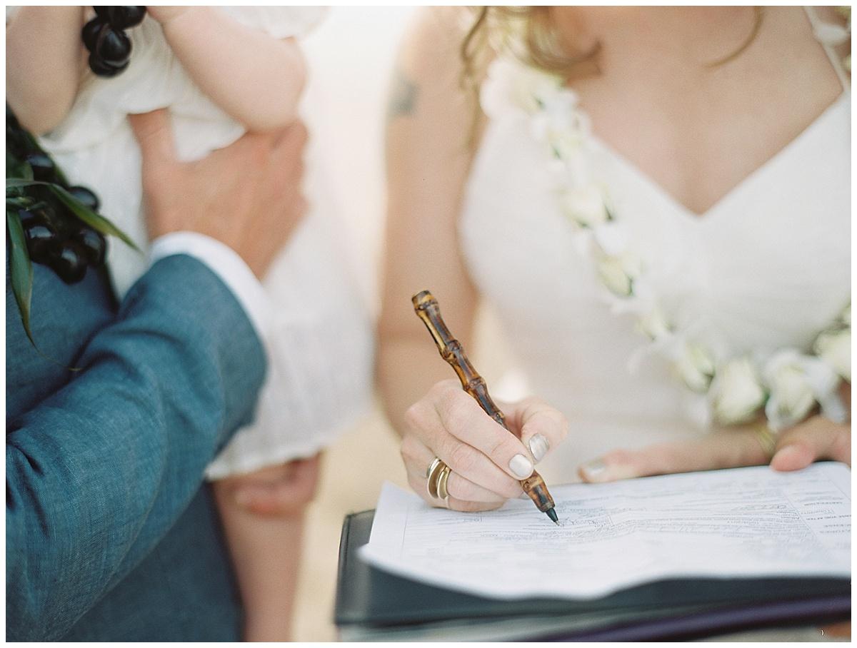 beach-elopement-bride-signing-license-bamboo-pen.jpg
