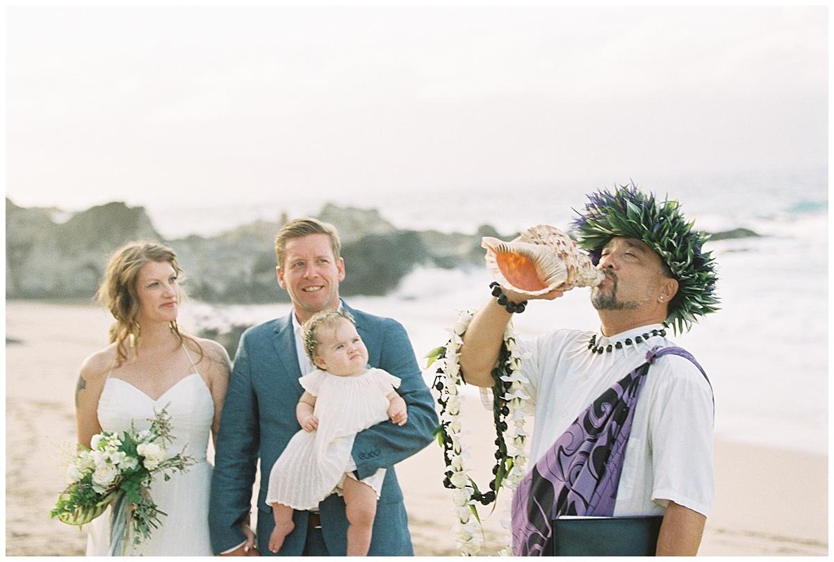 beach-elopement-ceremony-hawaiian-officiant-blowing-conch-shell.jpg