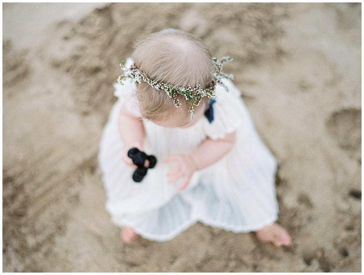 beach-elopement-flower-girl-holidng-kukui-nut-bracelet-flower-crown.jpg