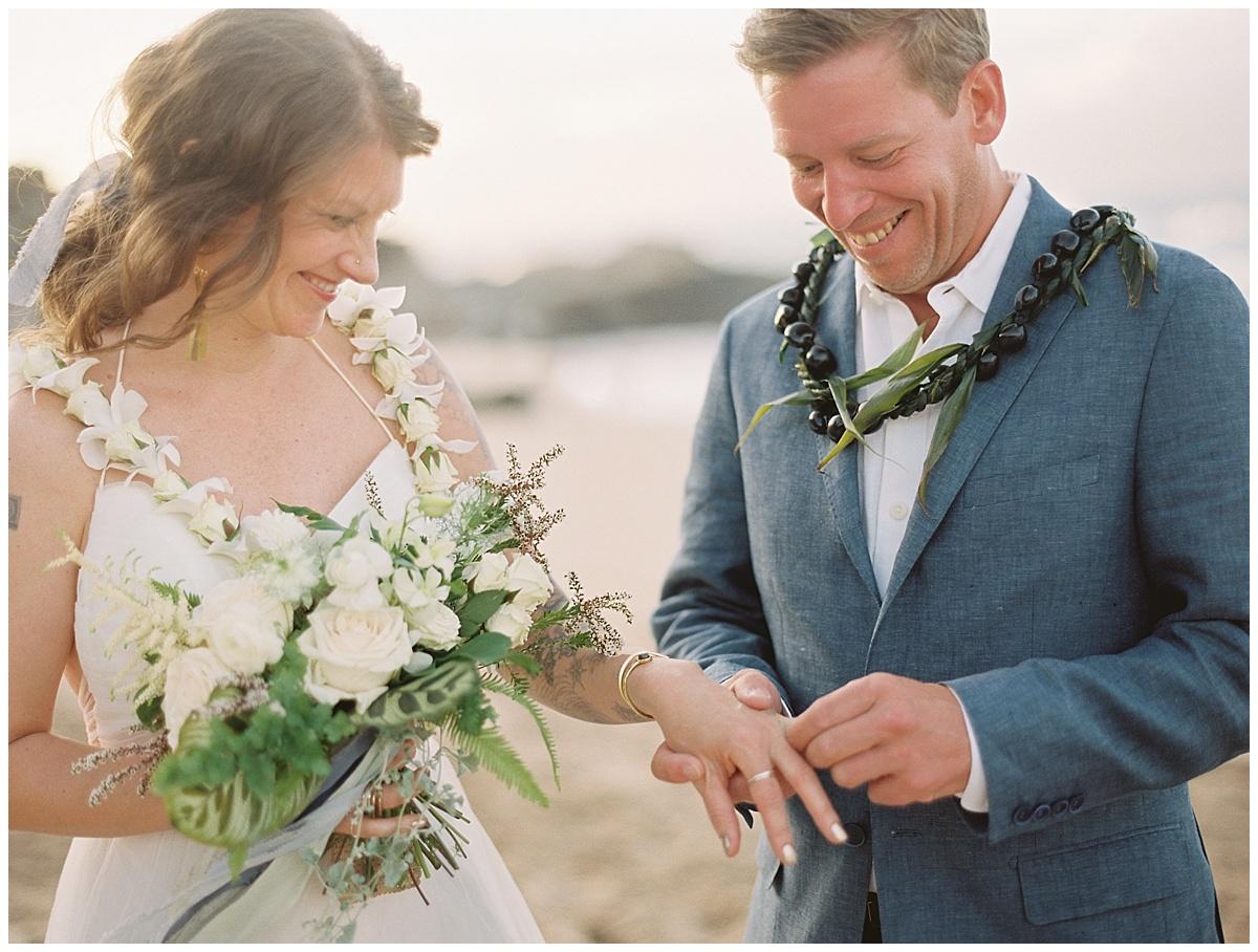 beach-elopement-groom-putting-ring-on-brides-finger.jpg