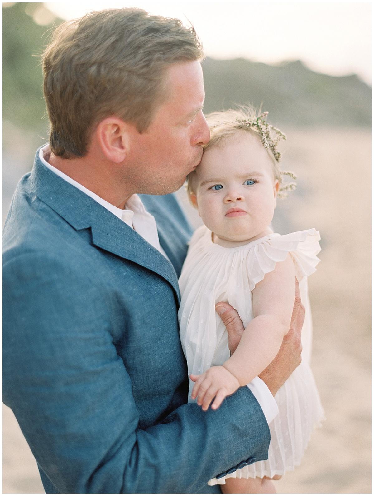 beach-elopement-groom-kissing-baby-daughter-blue-suit.jpg