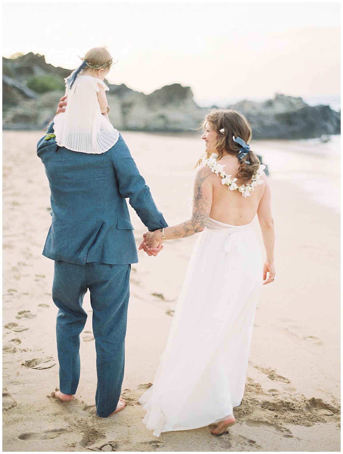 beach-elopement-maui-bride-groom-walking-baby-on-shoulders.jpg