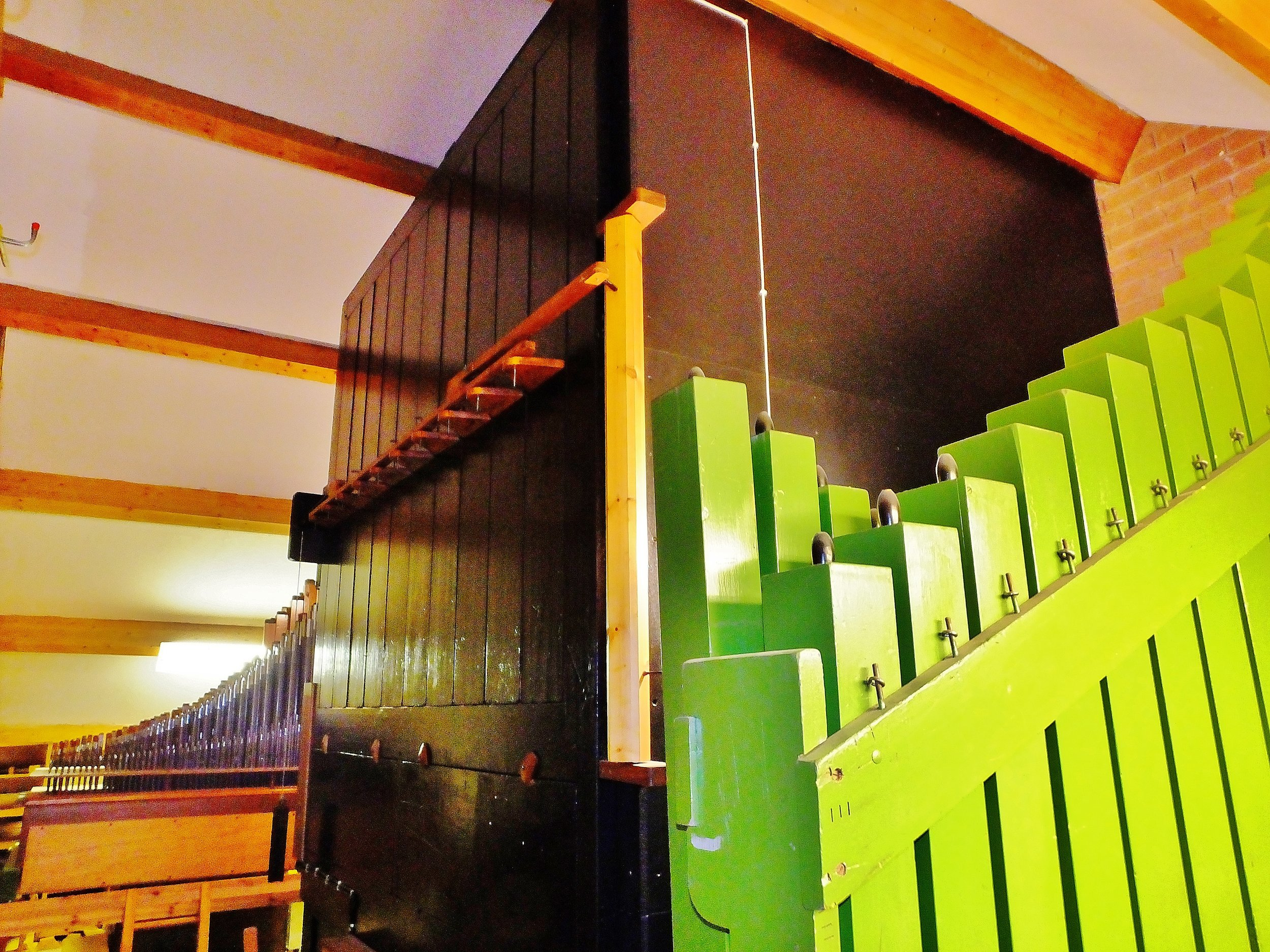 This is a good view of the pipes in the Organ Loft. In the background are metal pipes of the Great Organ. The Black very large cabinet is the Swell box which contains many pipes and the louvres can be opened to increase the volume. The green pipes are the bourdon pedal pipes