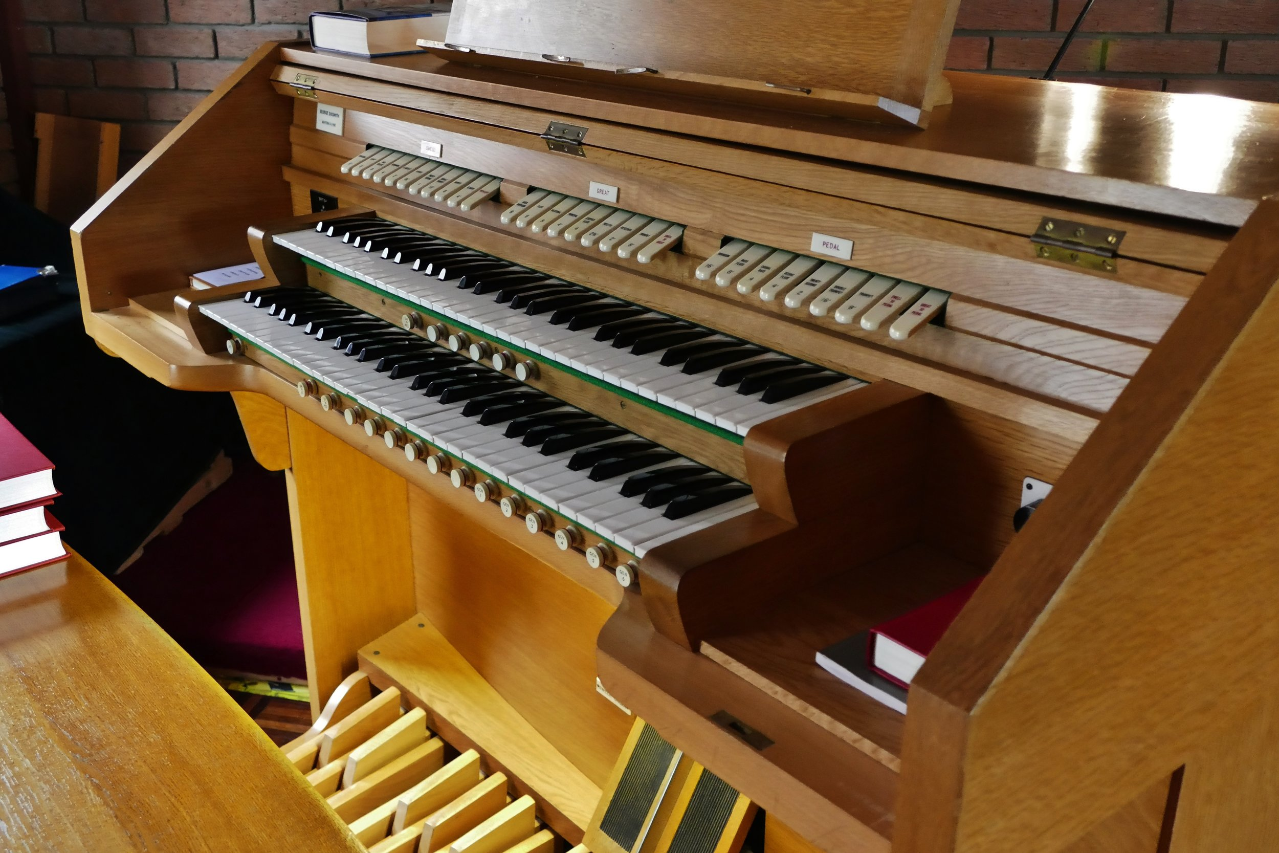 This is the Organ Console( The Keyboards). It has two keyboards. The top one is known as the Swell and can be adjusted for volume,. The bottom one is known as the Great and has open pipes some of which are quite loud. The pedal board is really another keyboeard but operated by the feet!. All three can be coupled together . There are also more then twenty different Stops( types of pipe. This gives the instrument a great amout of versatility to provide music for all types of hymns and songs