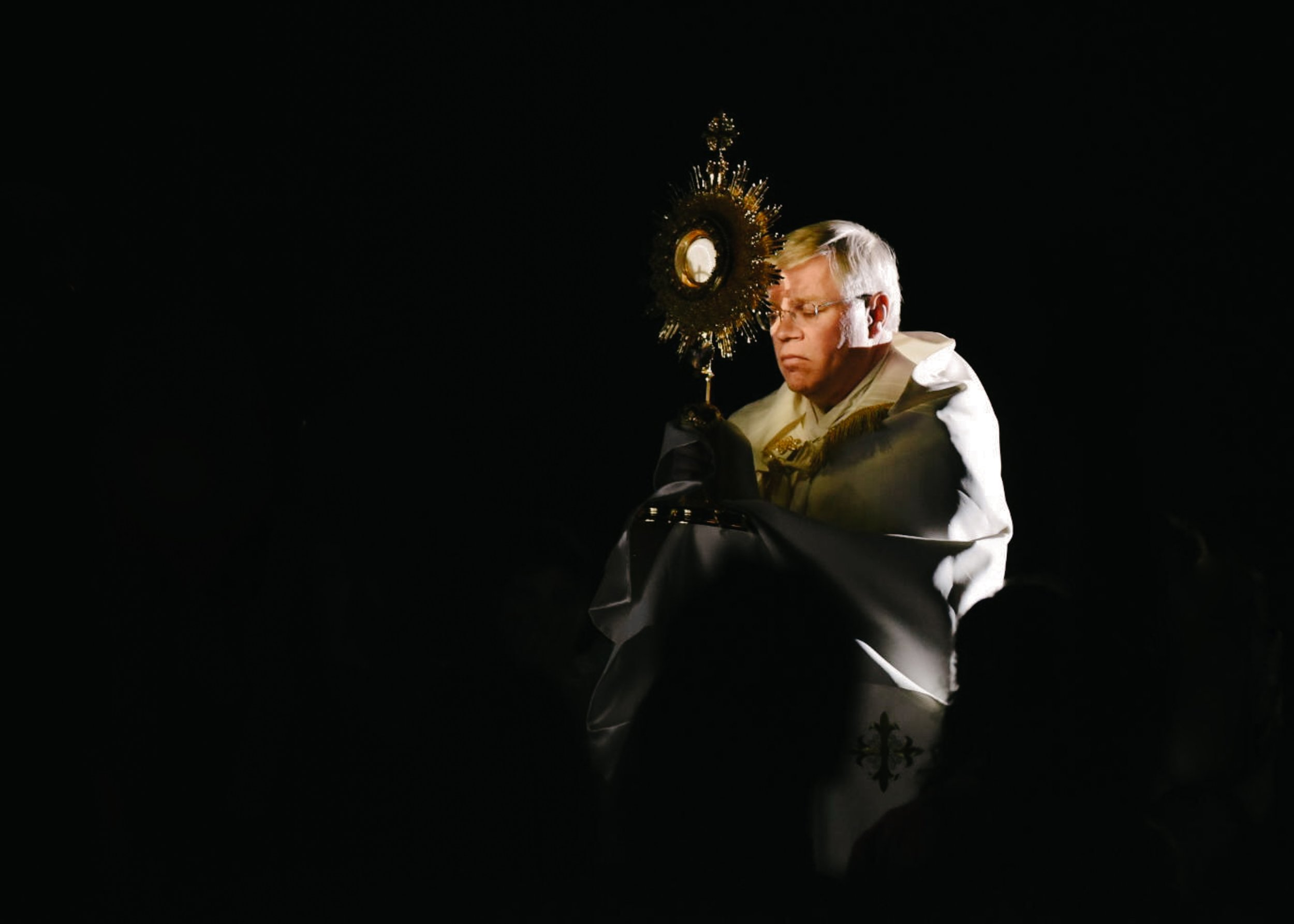 Priest carrying the Monstrance
