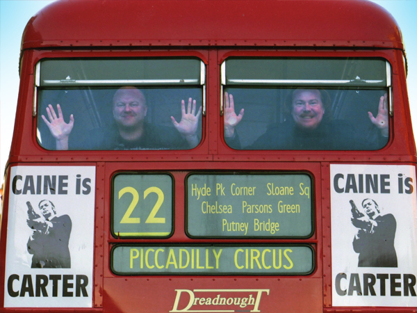 "Wilson and Irwin showing off the ""Caine Is Carter"" bus graphics, in homage to the original 1971 London bus promo campaign."