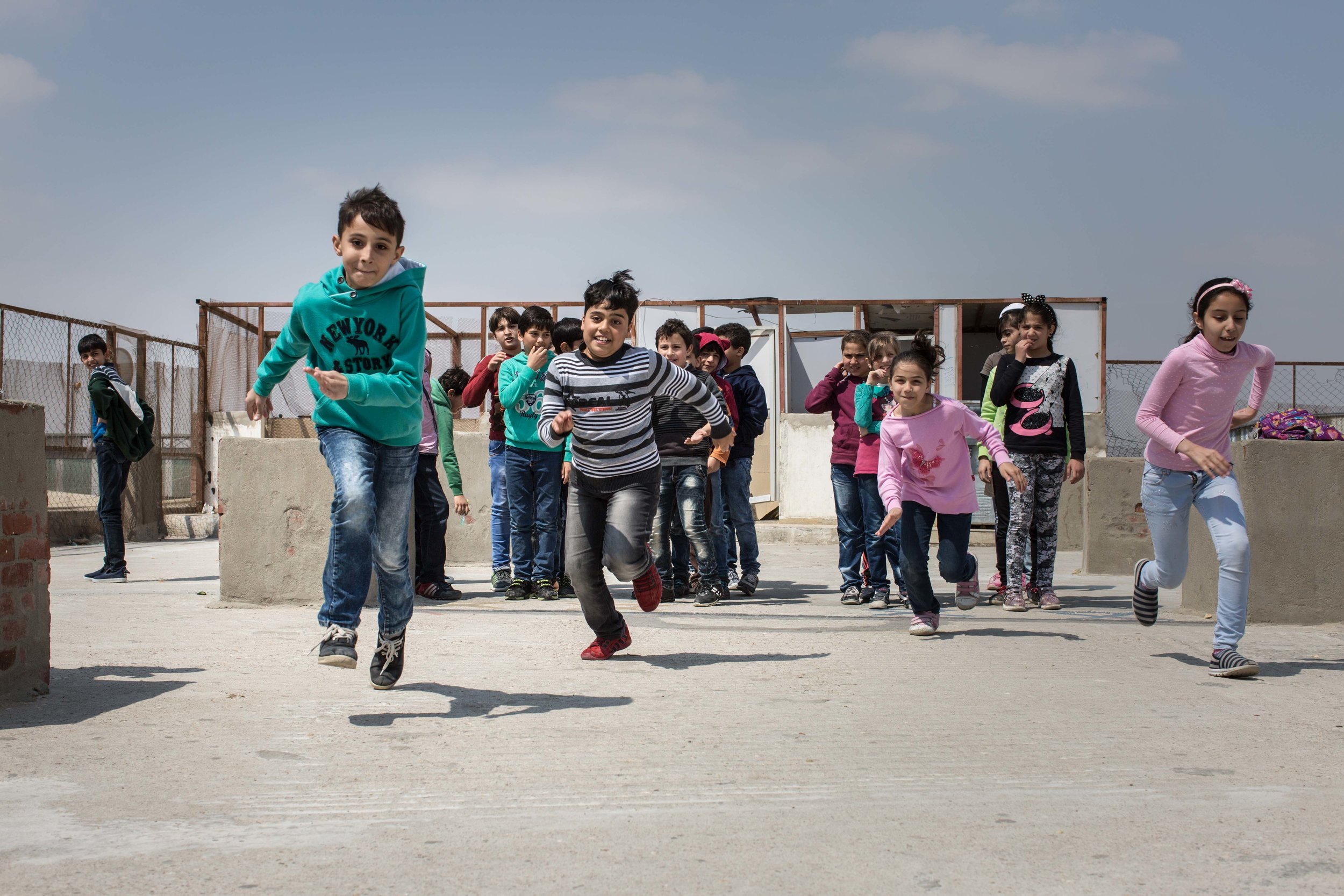 Children race on the rooftop of a community school for Syrian refugees in the Obour district of Cairo, Egypt