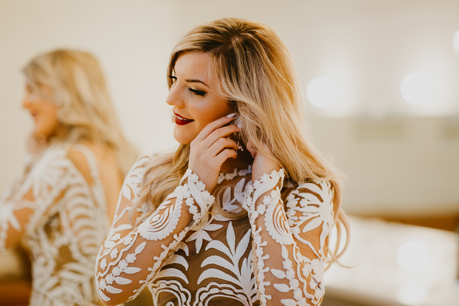 bride getting ready images putting on earrings + boho + hollywood glam hairstyle + makeup