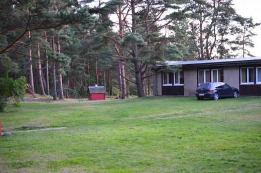 Rannakodu maja kõrval asuv tegevusala kiikude, liumäe ja mängumajaga