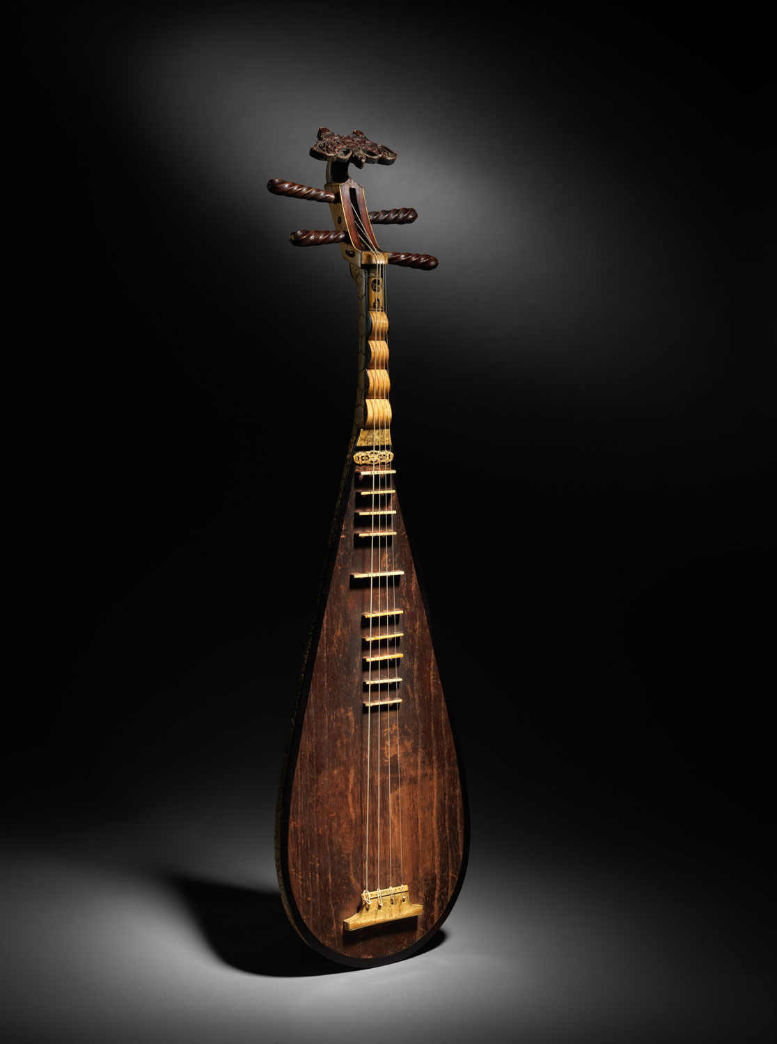 The Pipa    / A lute with four strings that dates back numerous centuries as a traditional and performance instrument.  / Tuning for the four strings are ADEA, from bottom to top. Notation is read in bass clef, with the lowest A starting at A2.  / Range is from the lowest A string (A2) to a high D in treble clef (D6).  / In order to play the Pipa, the player wears multiple plectra on their right hand, which essentially serve as picks in order to execute the many techniques attainable on this instrument:     Luen, a tremolo that can be played on multiple strings, played by all five fingers (There are multiple examples of this in the Pipa peace linked below)      Dzai, a muted note that sounds after the left hand plucks the highest string.      String bends, where the player changes the location of the finger on the left hand after plucking   / Linked below is a solo Pipa piece that demonstrates a lot of these techniques, as well as an interesting website that outlines the history and development of the instrument.   Picture courtesy of the Metropolitan Museum of Art
