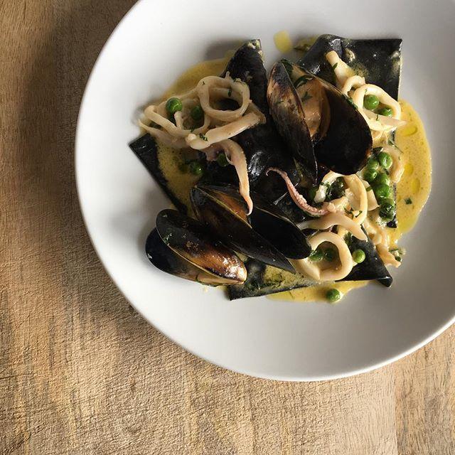 Squid ink ravioli, black mussels, calamari, saffron & peas