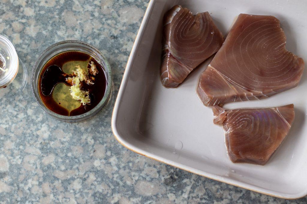 Coloca los filetes de atún en un plato profundo, y en un tazón pequeño el mirin, el aceite de sésamo, la salsa de soja y el jengibre para poder mezclarlo.