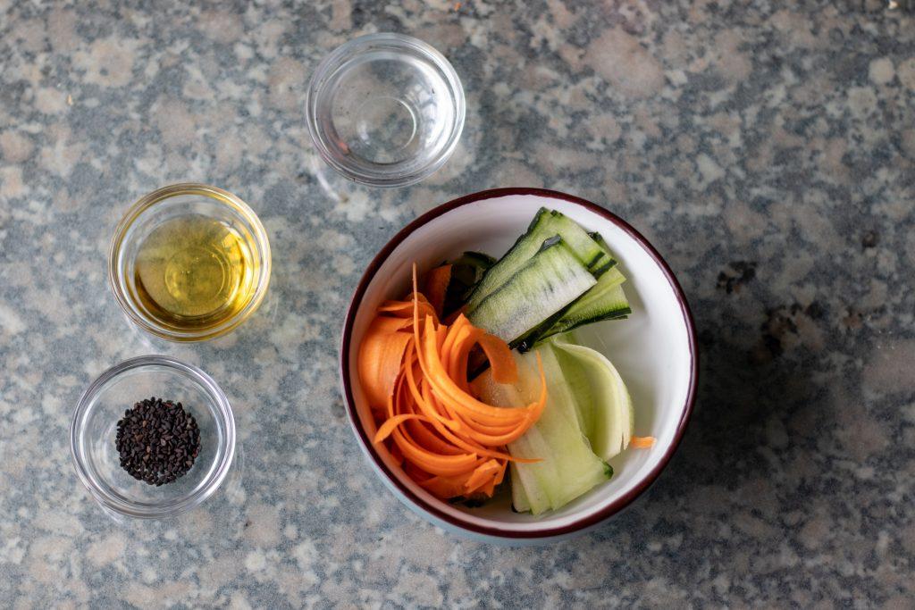 Ahora coloca los vegetales en un tazón e incorpora el vinagre de arroz, el mirin, el aceite de sésamo y las semillas.