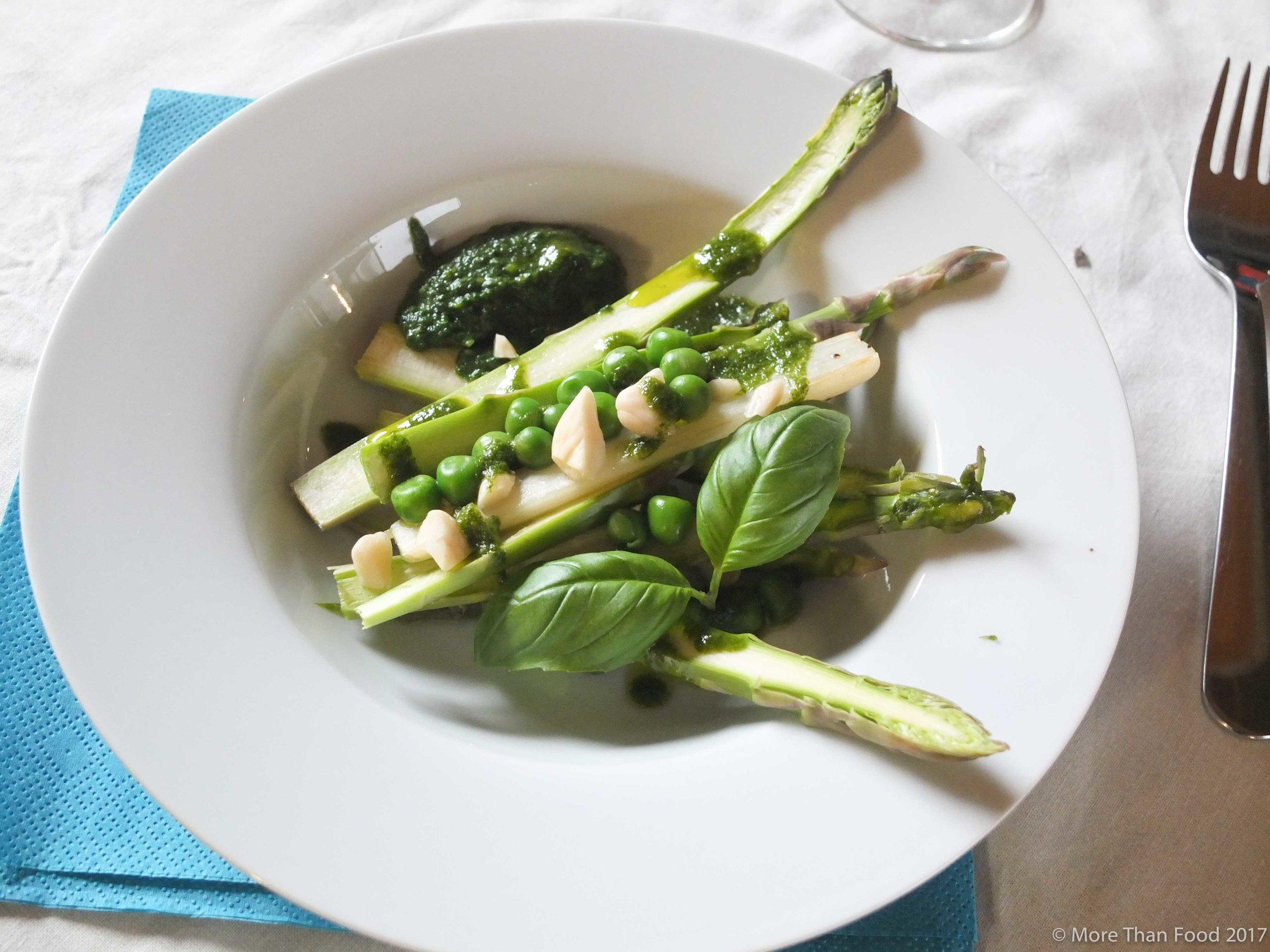 Duo van rauwe en gegrilde asperges met spinaziesaus, jonge erwten, basilicumolie en amandelen