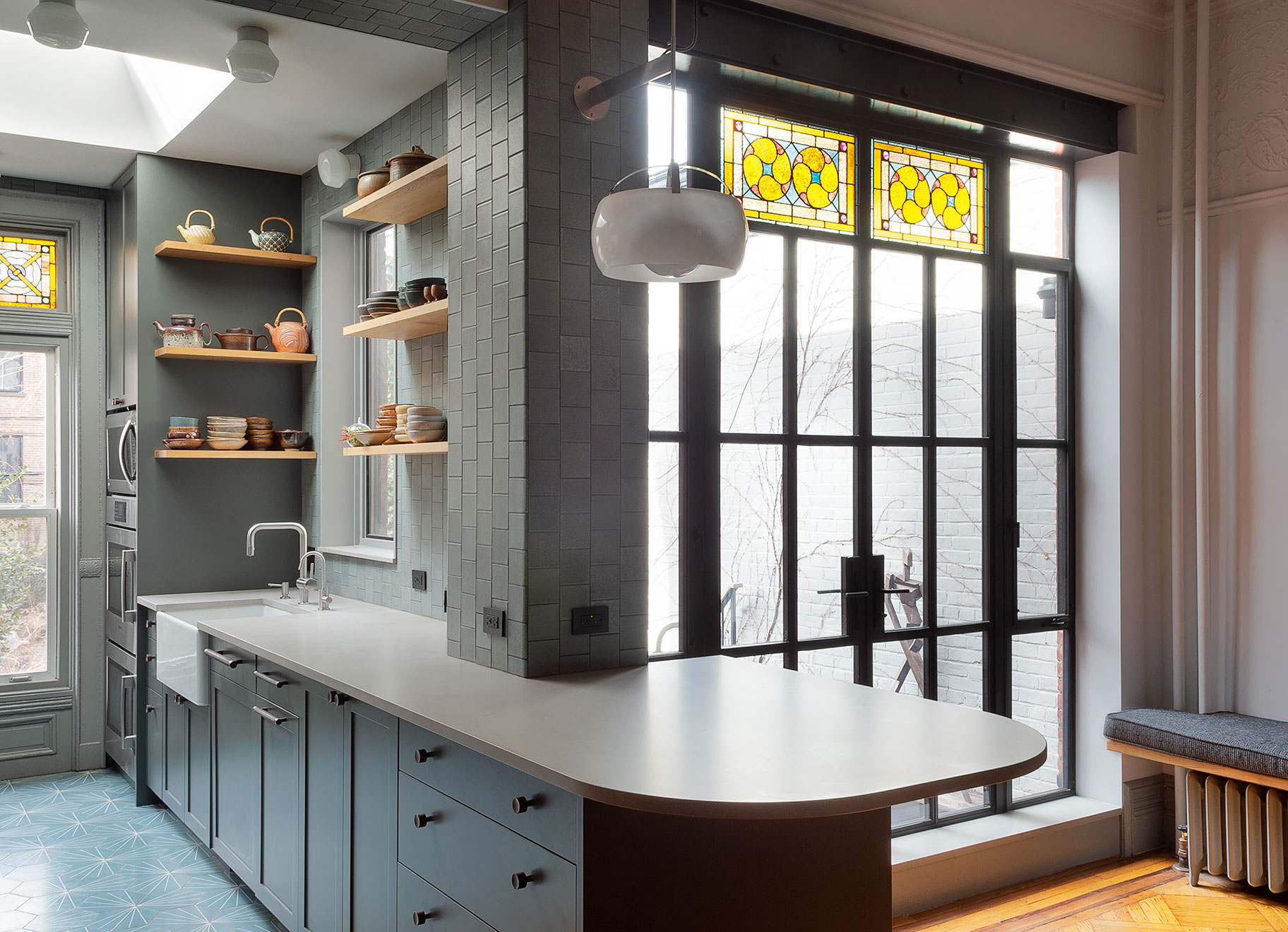 Doors and Passages  This venerable, Park Slope, Brooklyn, brownstone had numerous original details, many of which the owners wanted to keep. However, they wanted to mix in a modern sensibility, in a respectful way, while optimizing the house for their lifestyle. This included opening the kitchen to the dining room, adding a rear glass wall, deck, and secret powder room.