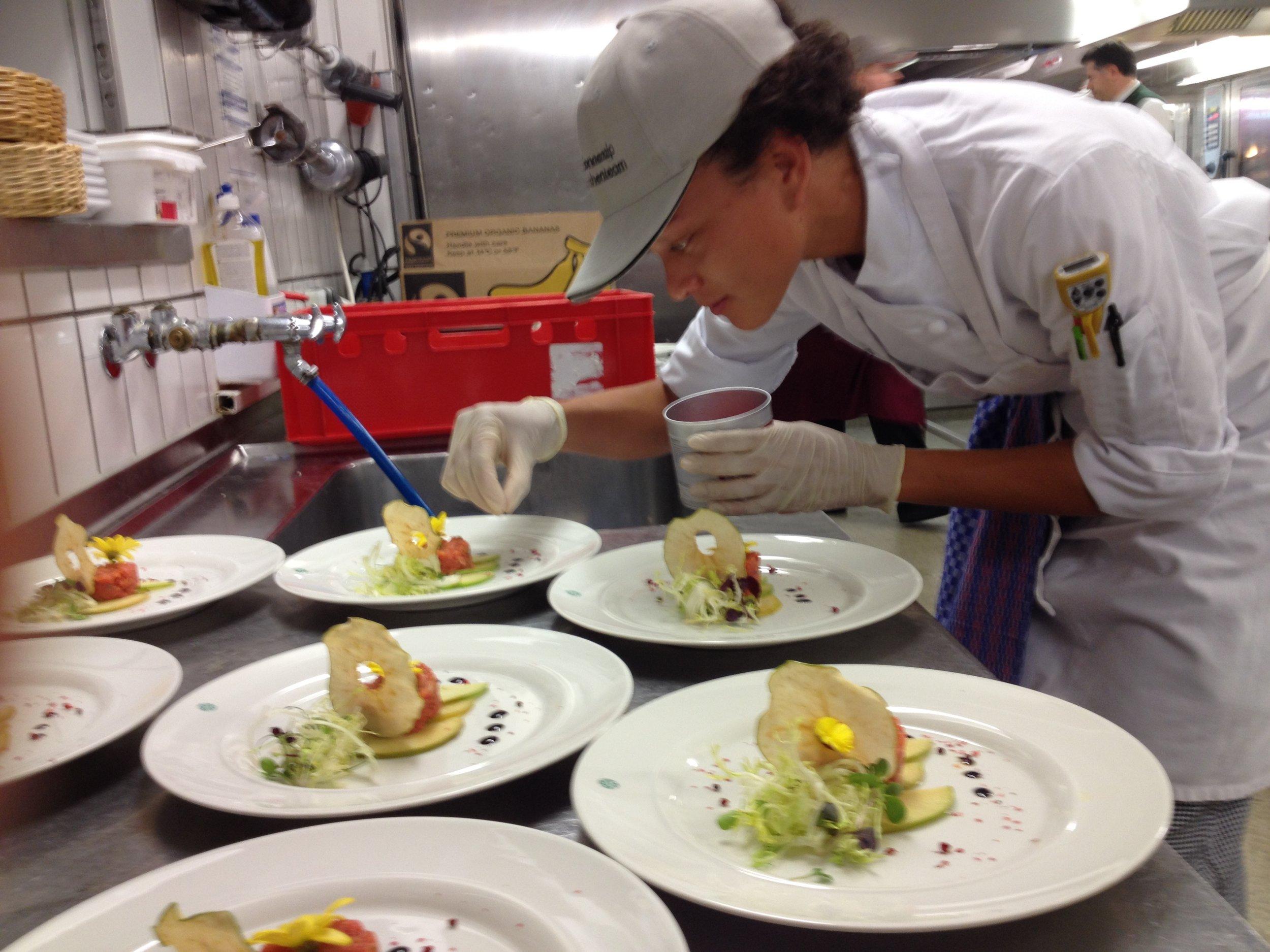 JWU student interns plates gourmet meal.