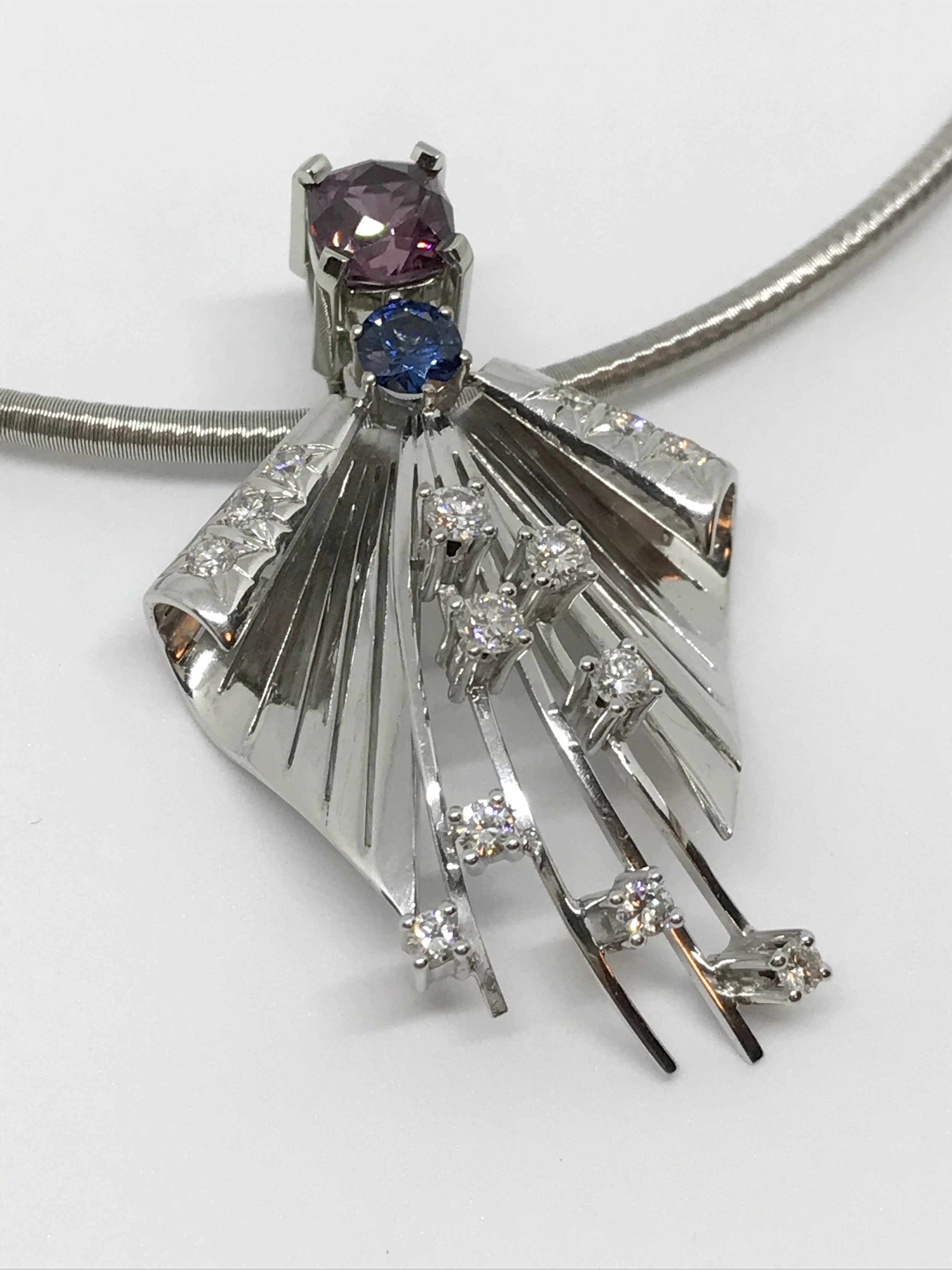 <b>Tranquility<br> Pendant</b><br>$8,476<br>18K White Gold<br>14 Brilliant Cut Diamonds<br> 1 Red and 1 Blue Spinel