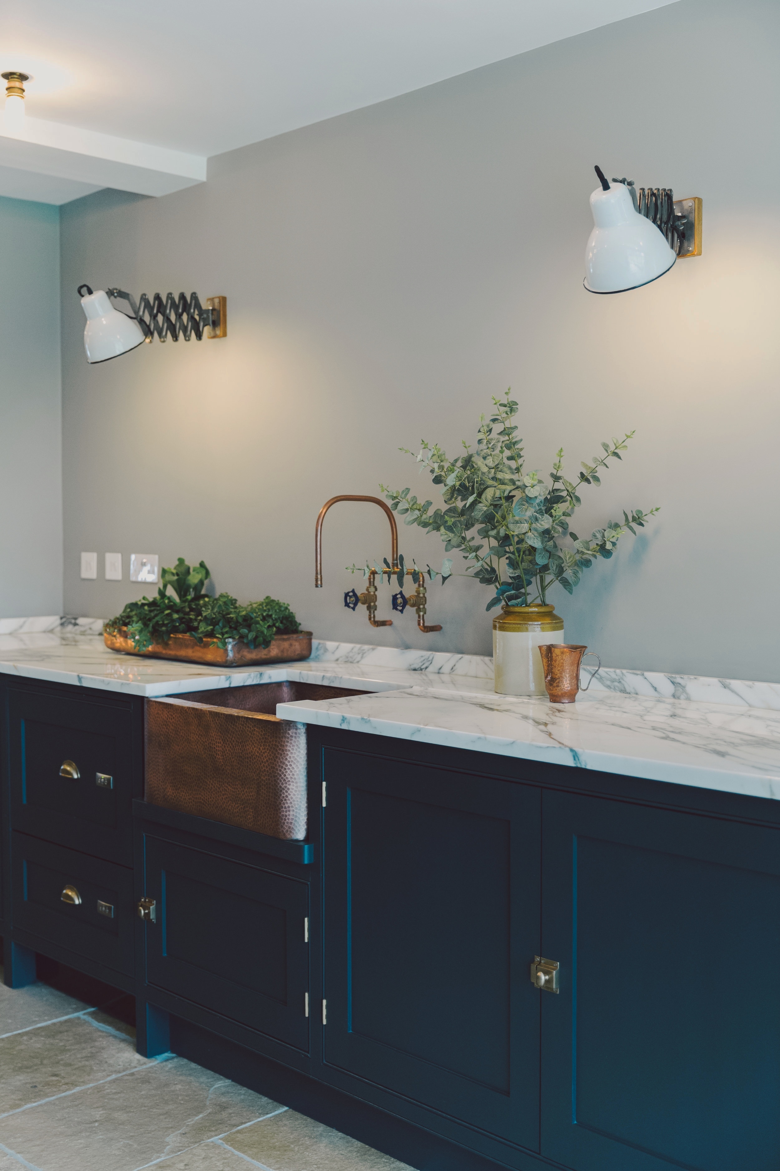 Dark grey kitchen with vintage wall lights and copper sink