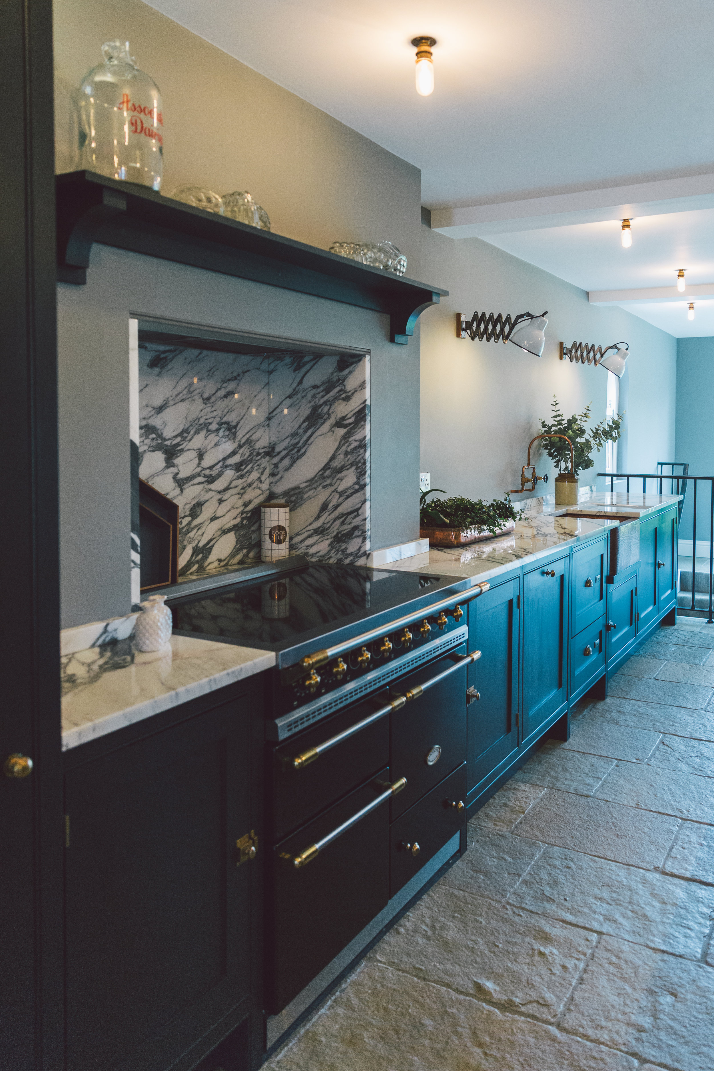 Dark grey Shaker kitchen with marble worktops, copper and brass details