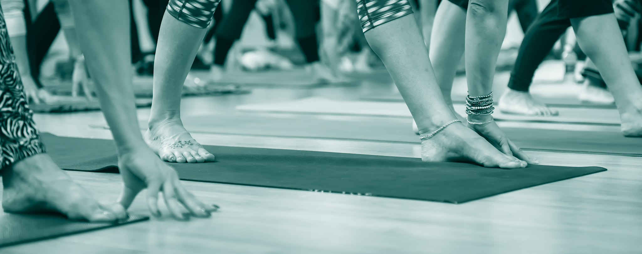 Blue tinted banner picture - showing the feet of people doing yoga