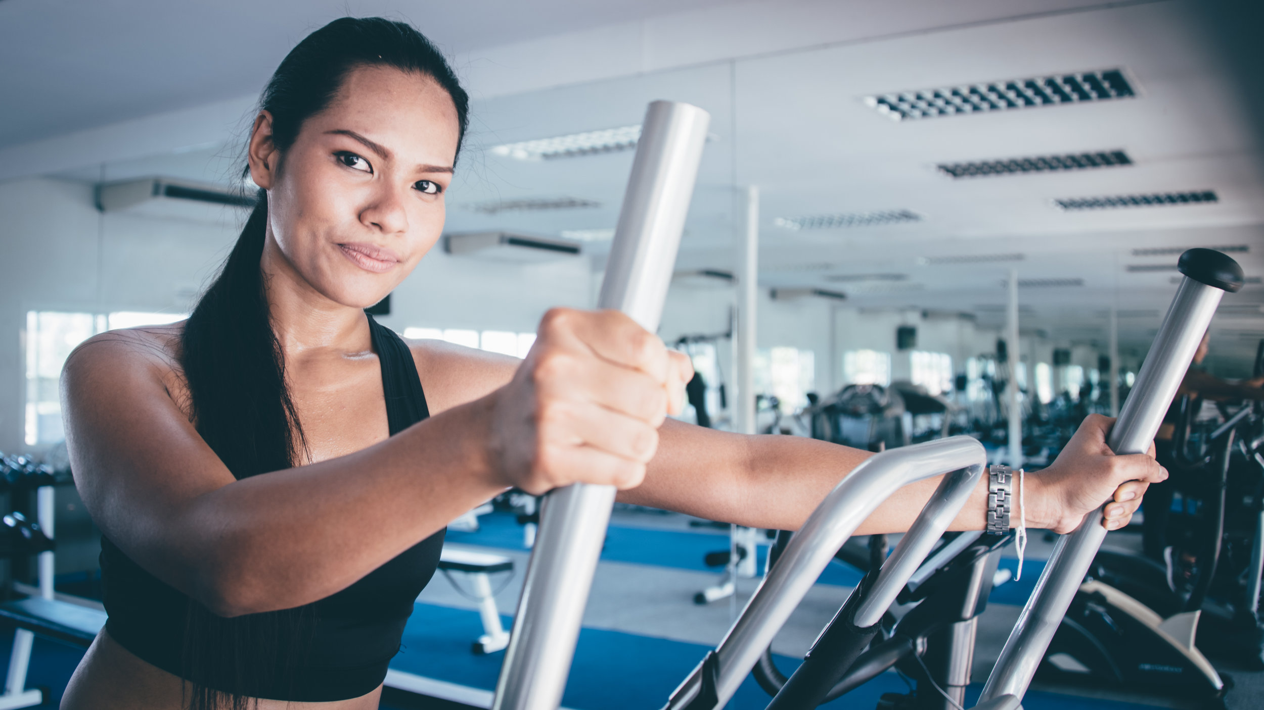 Lady training on elliptical machine