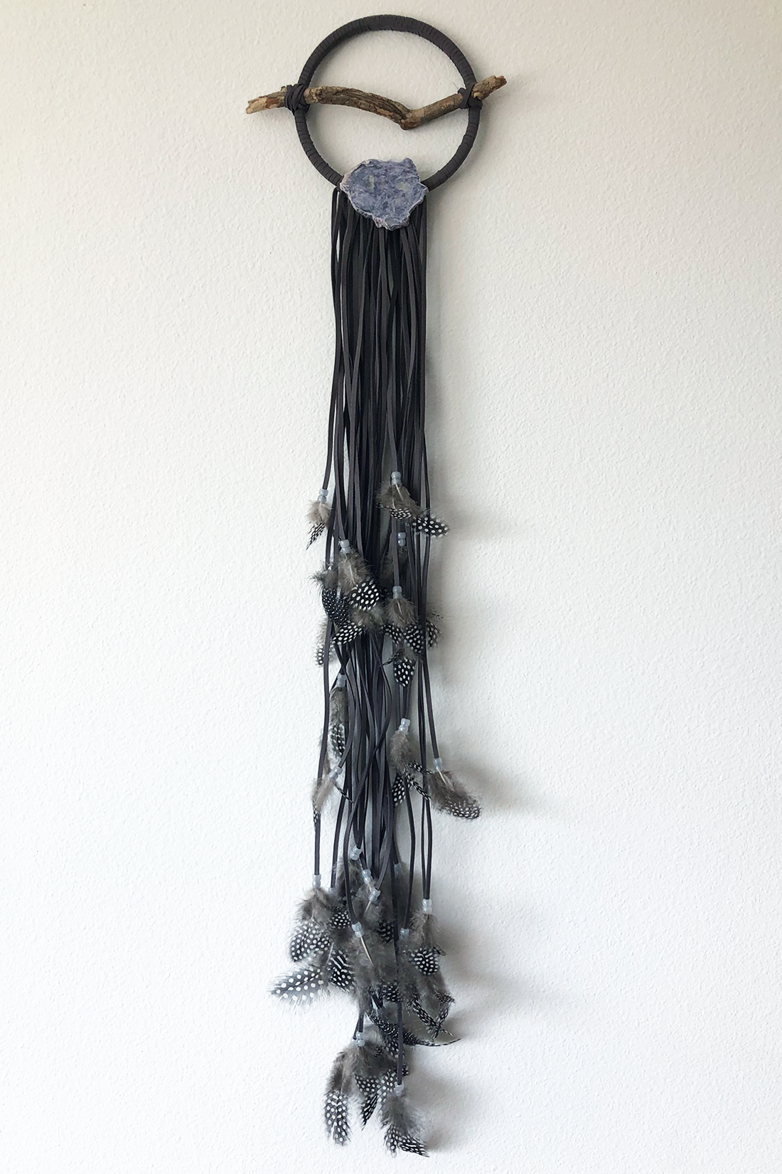 """Dreamcatcher, Small (6"""" diameter)  Grey faux suede cord, with black and white speckled feathers and glow-in-the-dark beads.  Stones: Charoite"""