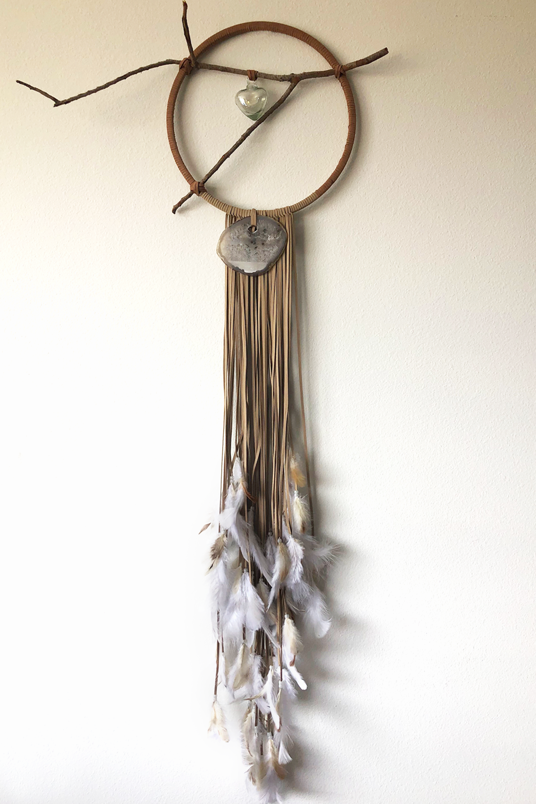 """Dreamcatcher, Large (14"""" diameter)  Slight two-toned dreamcatcher in faux suede medium tan and light tan cord with glow-in-the-dark white beads, and layered white and neutral colored feathers with glass heart center.  Stones: Agate"""