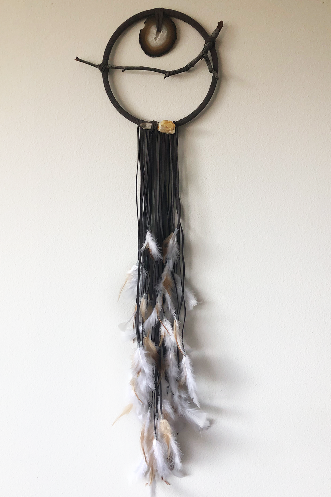 "Dreamcatcher, Medium (10"" diameter)  Grey faux suede cord and white glow-in-the-dark beads with layered white and brown feathers.  Stones: Agate, Crystal Quartz"