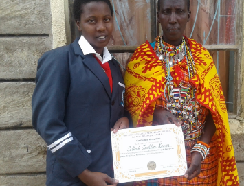 Selina (left) is congratulated by her mother after becoming Deputy Governor at Olomirani School for Girls