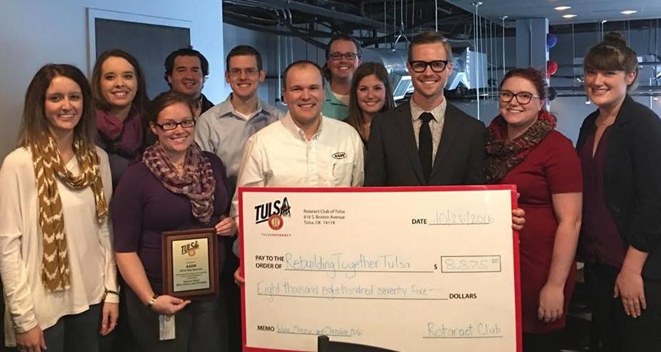 Tulsa Rotaract provides Rebuilding Together Tulsa a check for $8,875.00.