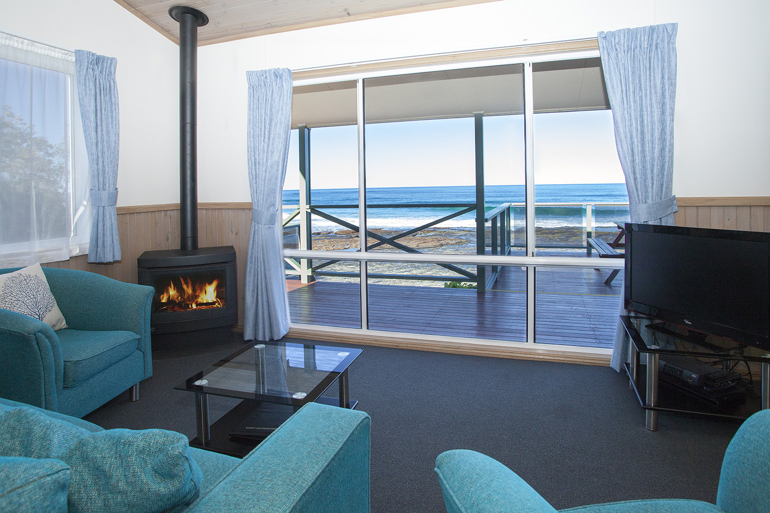 Oceanfront Deluxe, Chalet 11 living room with fire copy.jpg